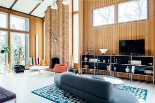 High ceilings and a full-length brick fireplace are complemented by extensive glazing.