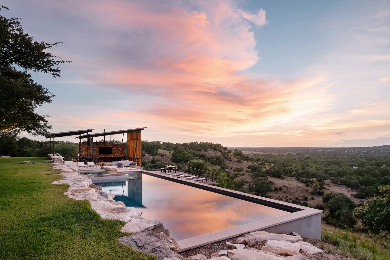 Outdoor, Trees, Back Yard, Large Patio, Porch, Deck, Stone Fences, Wall, Large Pools, Tubs, Shower, Shrubs, Swimming Pools, Tubs, Shower, and Boulders The wood-slatted louvers to provide shade from the setting sun and a breathtaking view.  Best Photos from An Old Texas Ranch Becomes a Spectacular Family Haven