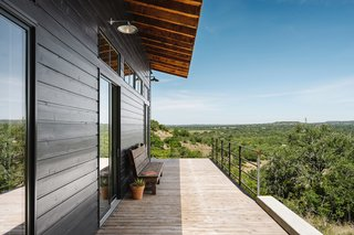 The wraparound deck boasts a view of the surroundings with shade provided by the eaves of the roof.
