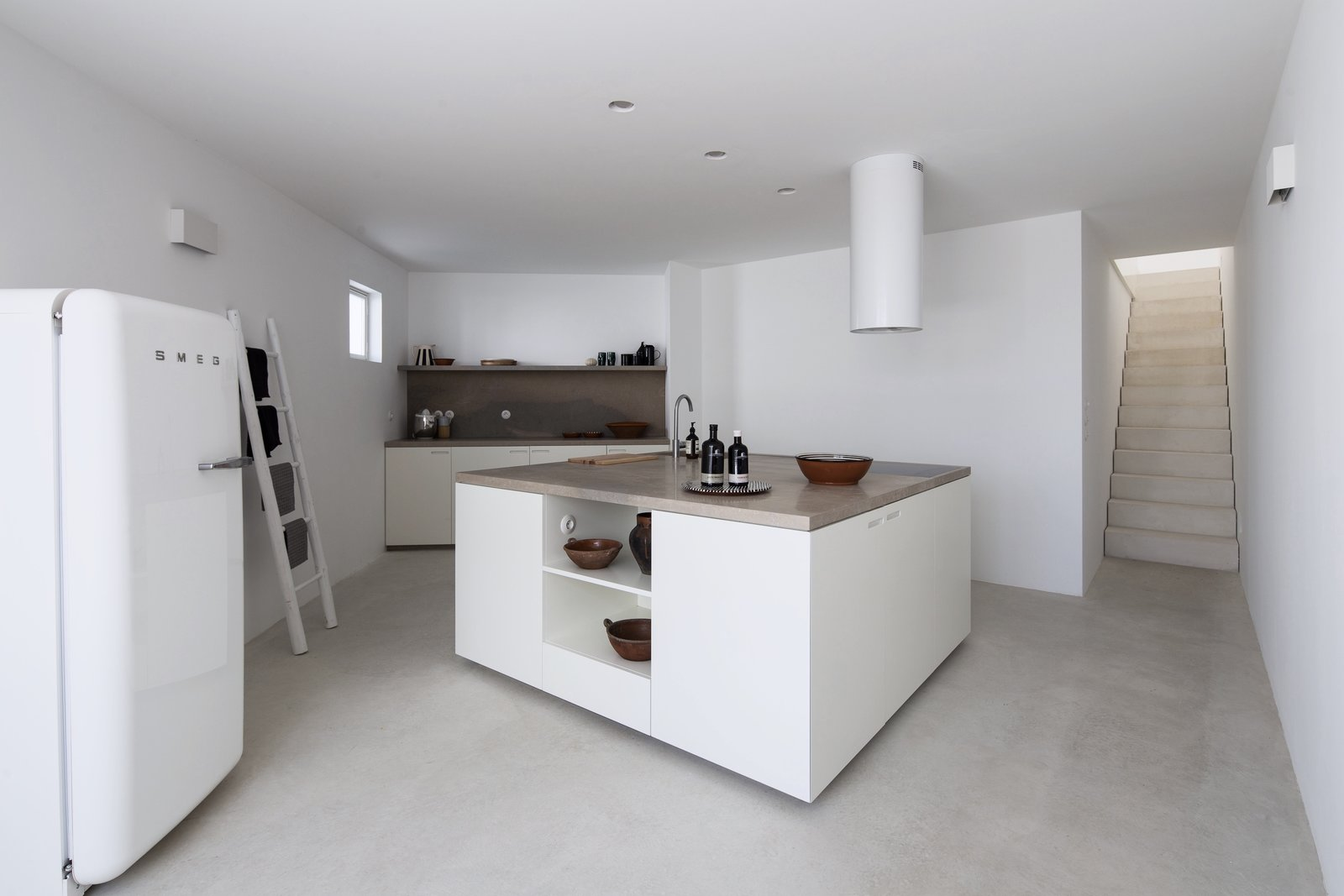 Kitchen, Refrigerator, Concrete, Recessed, Stone, Cooktops, White, Wall, and Range Hood The kitchen features a large central island with natural stone countertops and a stylish SMEG refrigerator.  Best Kitchen Wall Recessed Photos from Book This Idyllic Portuguese Home For Your Next Escape