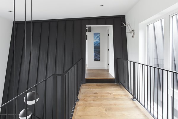 The sloped walls of the original home were integrated and combined with the extension. This was done via the connection of a double-height entry and a second-floor bridge.