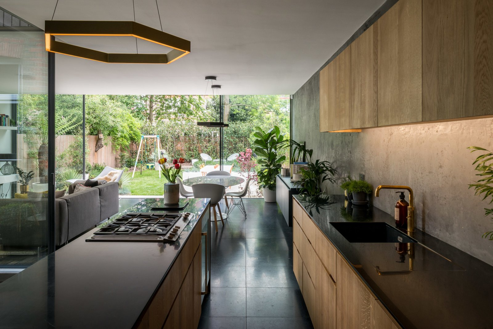 Kitchen, Terrazzo, Undermount, Pendant, Wood, Cooktops, and Concrete Arranged in an open plan with dark, terrazzo-tiled flooring, the main living space consists of the kitchen, dining area, and living room.     Kitchen Cooktops Undermount Concrete Photos from A Swoon-Worthy London Apartment Is Listed For £1.8M