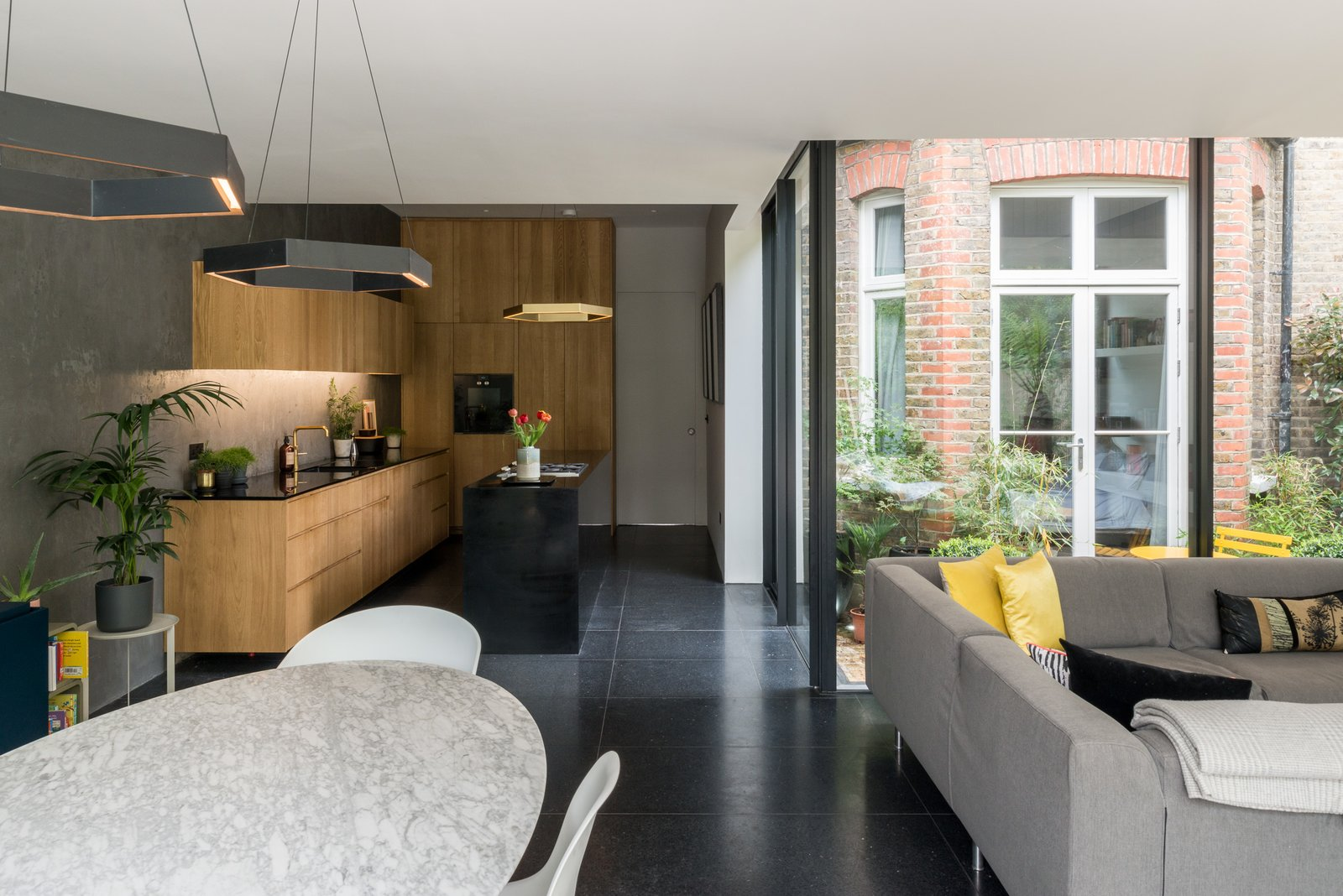 Living Room, Terrazzo Floor, Sectional, Pendant Lighting, Chair, and Table An overview of the open-plan interior space.  Photo 4 of 11 in A Swoon-Worthy London Apartment Is Listed For £1.8M