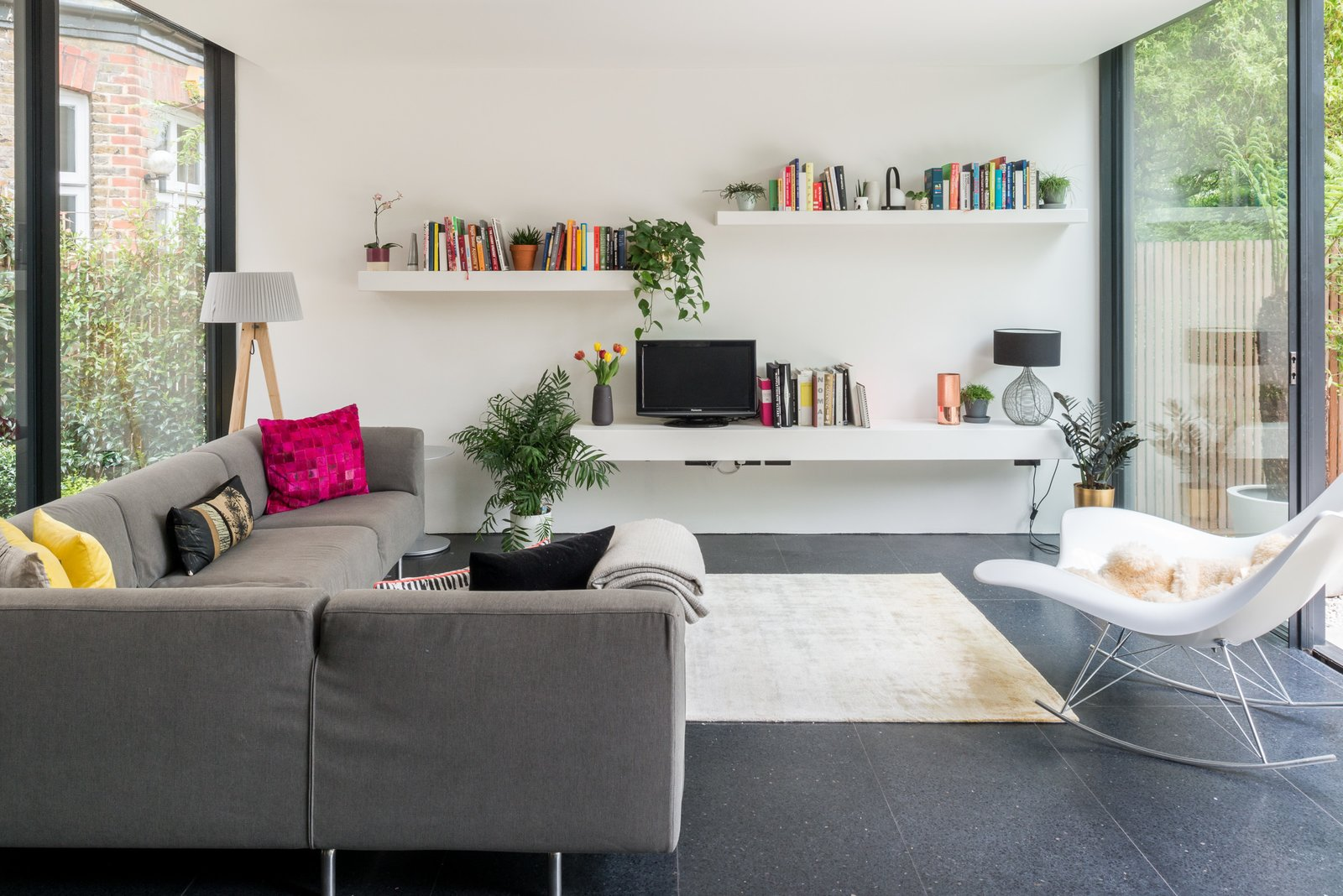 Living Room, Rug Floor, Sectional, Terrazzo Floor, Shelves, Chair, Table Lighting, and Floor Lighting The living room is bright and airy thanks to floor-to-ceiling glazing and a crisp white wall.     Photos from A Swoon-Worthy London Apartment Is Listed For £1.8M