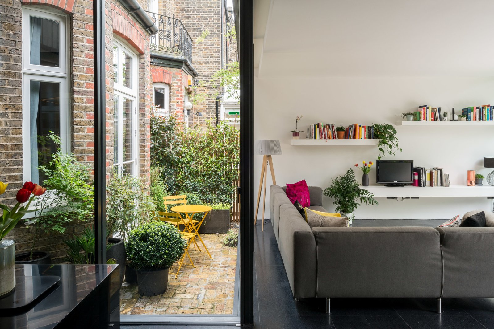 Living Room, Terrazzo Floor, Sectional, Floor Lighting, Shelves, and Table Lighting On the other side of the sitting room is a small courtyard, framed by internal glazing and accessed via a glazed side-door.     Photo 6 of 11 in A Swoon-Worthy London Apartment Is Listed For £1.8M