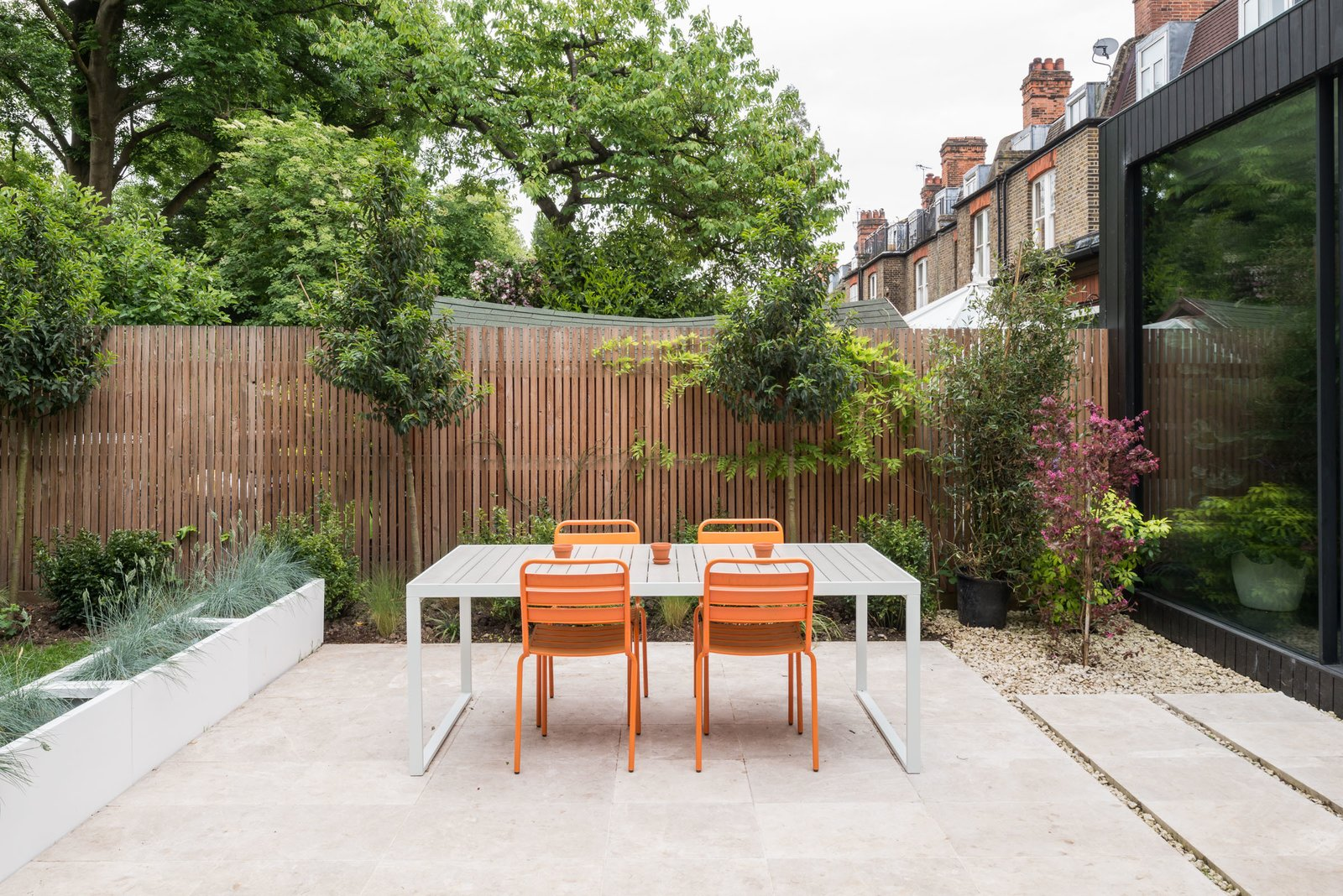 Outdoor, Horizontal Fences, Wall, Hardscapes, Shrubs, Trees, Gardens, Back Yard, Large Patio, Porch, Deck, and Wood Fences, Wall The sliding doors open to the marble-paved terrace.     Photo 10 of 11 in A Swoon-Worthy London Apartment Is Listed For £1.8M