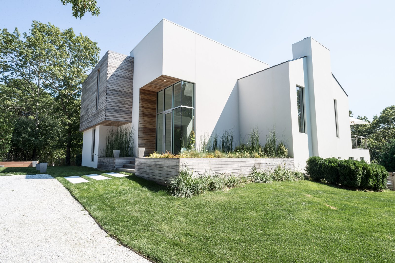 Exterior, Gable, Wood, House, Beach House, Flat, Metal, and Concrete Essentially, the entrance was kept in the same spot, with the chimney to the far right side.     Best Exterior Metal Wood Gable Concrete Photos from Before & After: A Dated Hamptons Home Is Now a Luminous Retreat