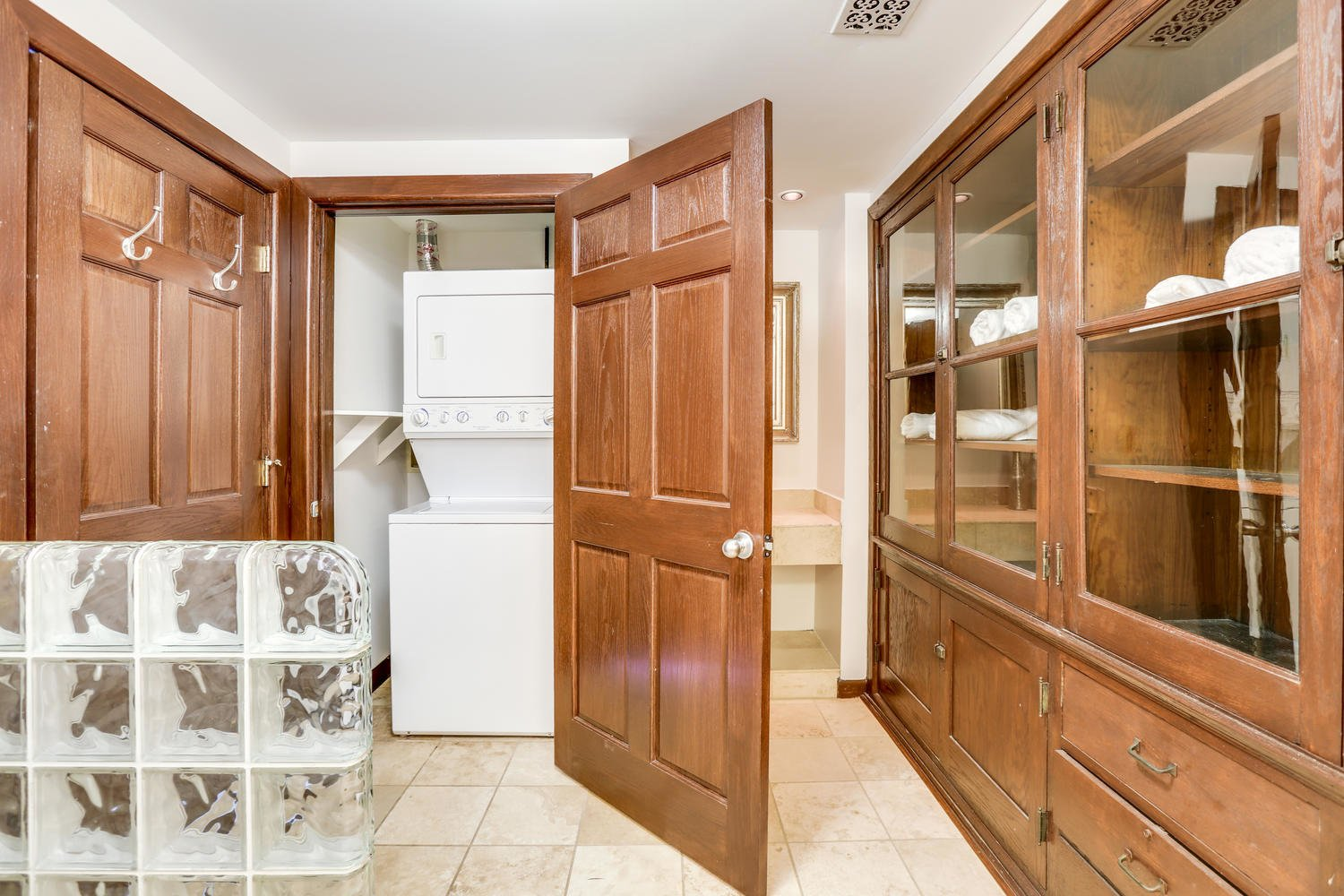 Laundry Room, Wood Cabinet, and Stacked The bathroom conceals the washer/dryer, and also benefits from original cabinetry.     Photo 8 of 9 in Grab This Dazzling Detroit Loft in a Historic School Building For $450K