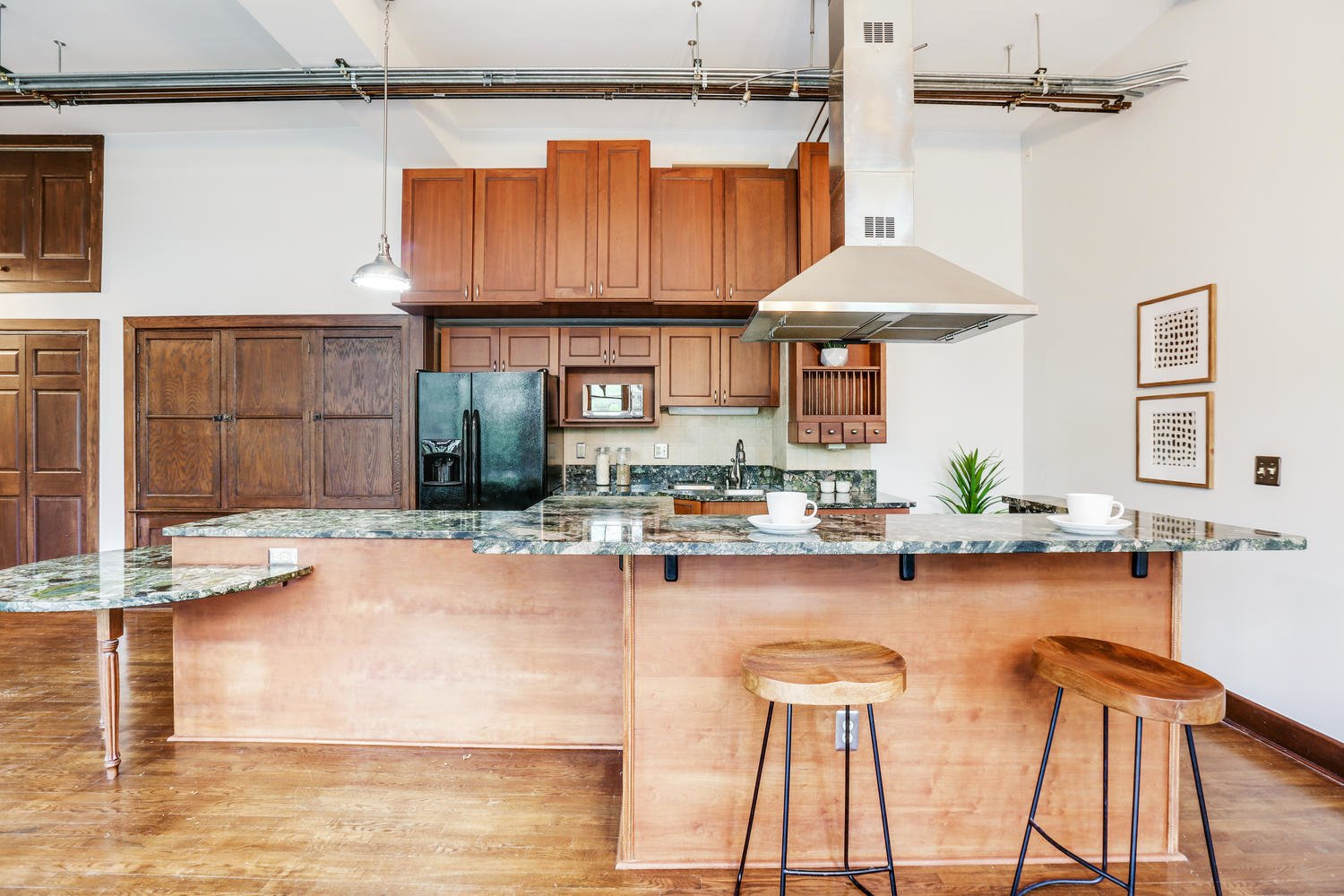 Kitchen, Quartzite Counter, Range Hood, Refrigerator, Medium Hardwood Floor, Pendant Lighting, Undermount Sink, Microwave, and Wood Cabinet A look at the open kitchen.  Photo 1 of 9 in Grab This Dazzling Detroit Loft in a Historic School Building For $450K