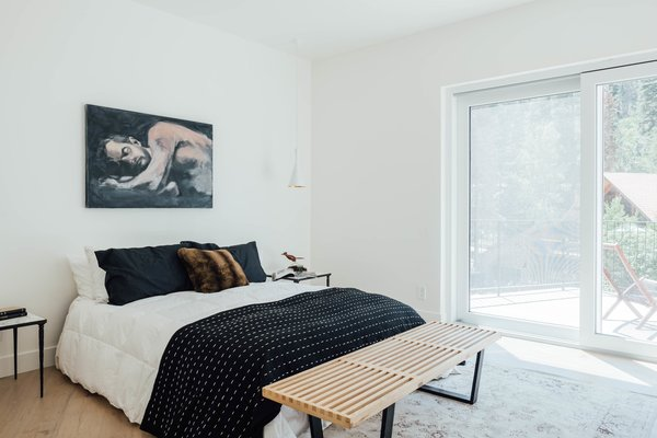 Upstairs, the home features four bedrooms and four baths. Here, large sliding doors provide ample natural light and easy access to an outdoor patio.