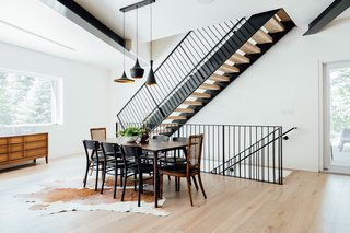 Tom Dixon's pendant lighting over the dining table perfectly helps define the space, further adding to the striking balance of light and dark. A custom staircase leads through the three levels of the home.