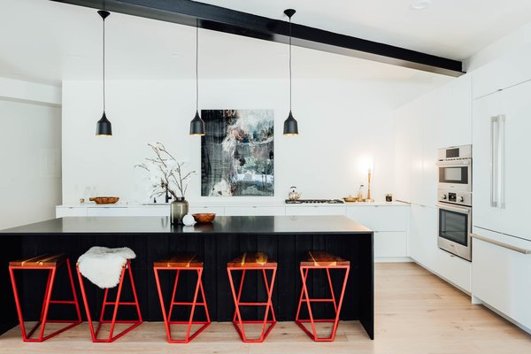 Black and white elements intersect in this clean, modern kitchen. Often, black and white kitchens benefit from a pop of color, seen here with these bright red barstools.