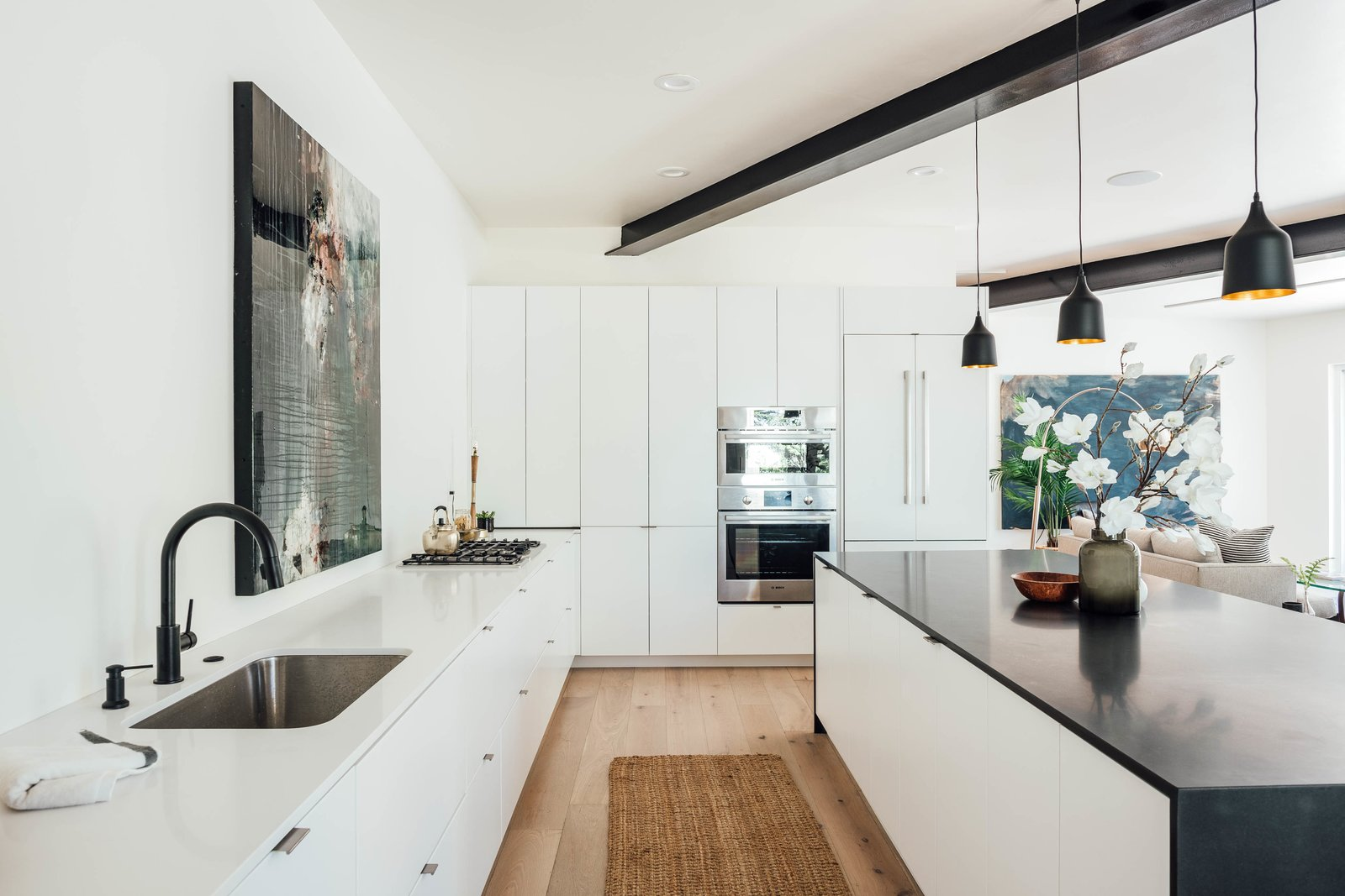 Kitchen, Recessed, Light Hardwood, Wall Oven, Refrigerator, Pendant, Undermount, White, Rug, and Cooktops The open kitchen provides plenty of workspace and storage.  Kitchen Cooktops Undermount Wall Oven Rug Photos from This Passive House in Park City Just Hit the Market For $1.1M