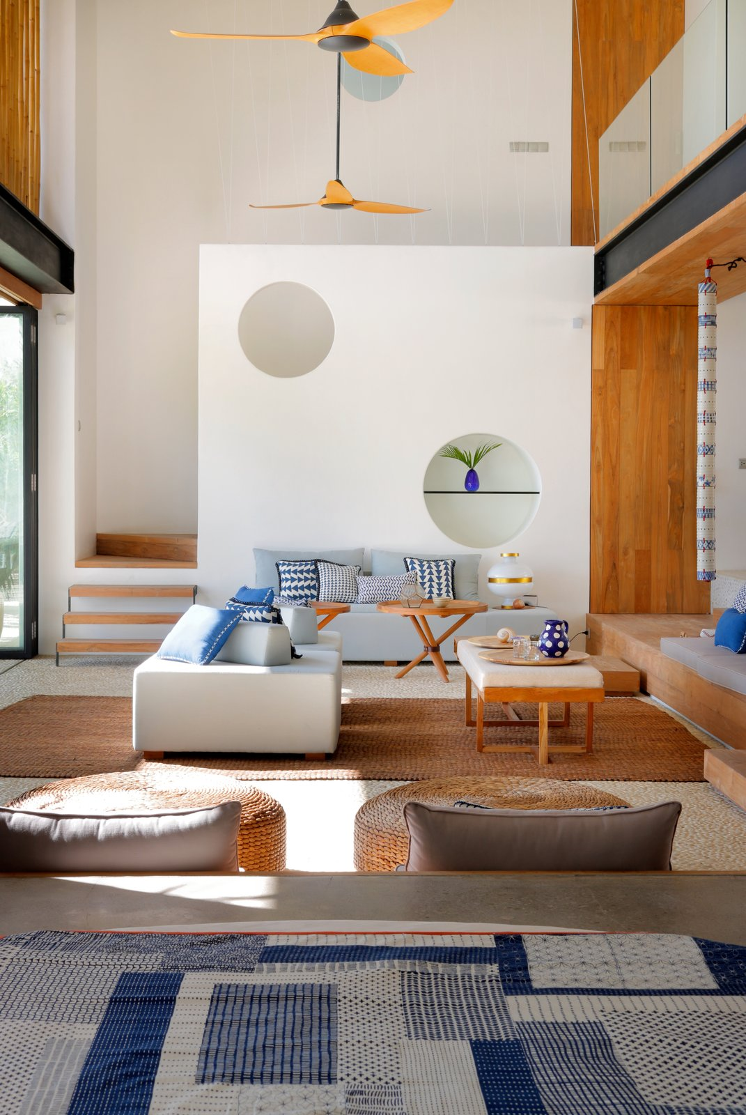"Living, Sofa, Ottomans, Coffee Tables, and Rug ""Blue and white tones came up very often during our conversations, and the fact that the property was sitting right on the ocean made it feel like a good fit for their vision,"" adds Audrito.    Best Living Photos from Fall in Love With Bali at This Tropical, Modern Retreat"