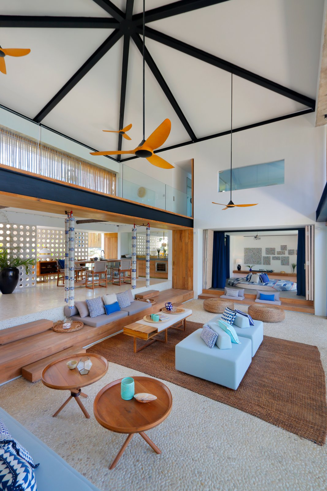 Living Room, Coffee Tables, Sofa, Rug Floor, and Ottomans Ceiling fans help cross-ventilation and allow the double-height communal space to stay cool.     Photo 6 of 19 in Fall in Love With Bali at This Tropical, Modern Retreat