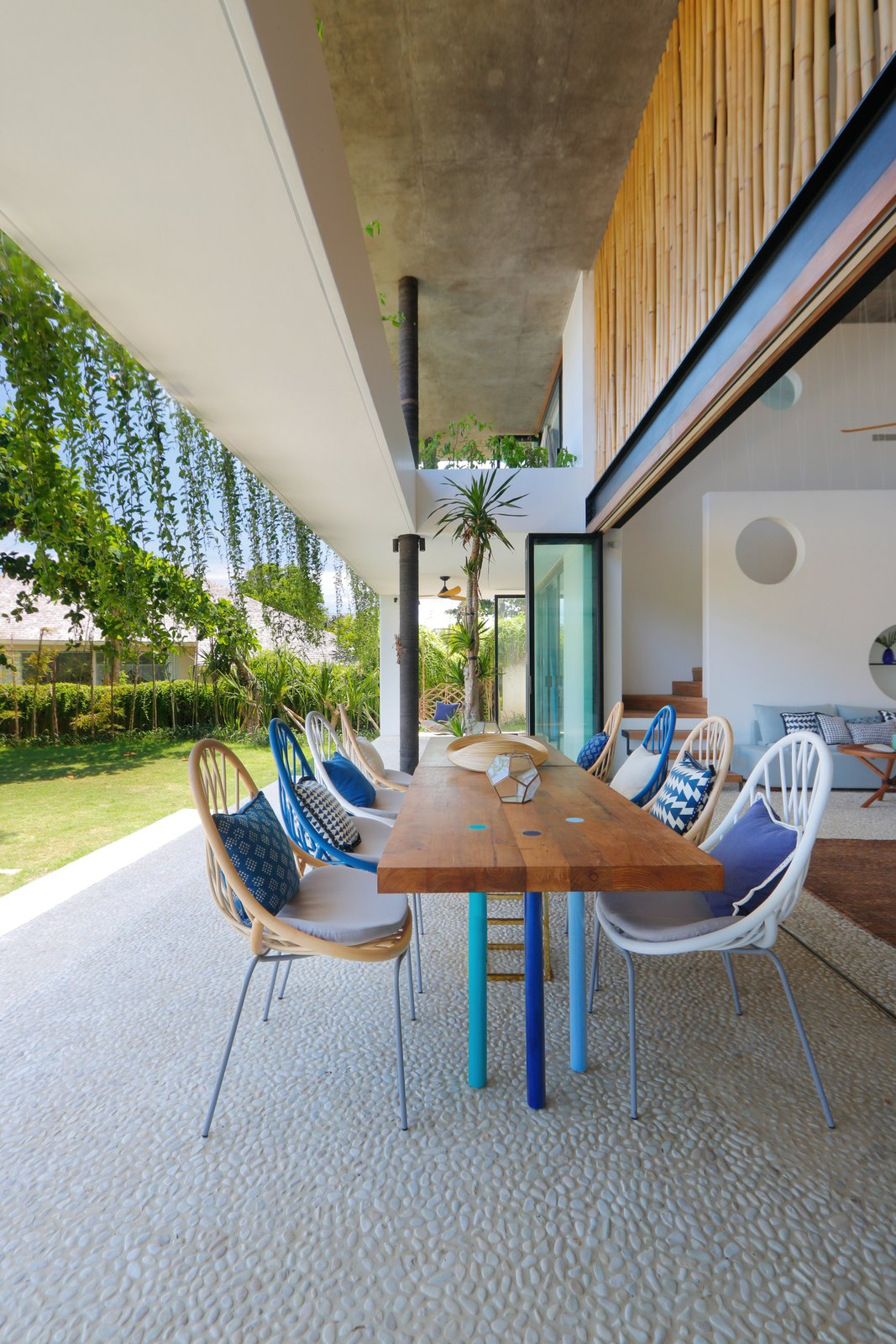 Outdoor, Grass, and Large Patio, Porch, Deck Meals can be had al fresco in the indoor/outdoor patio. The concrete/pebble floors are used both inside and outside the home to tie both spaces together.    Photo 8 of 19 in Fall in Love With Bali at This Tropical, Modern Retreat