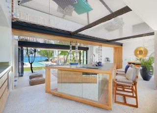 The home opens to its surroundings for true indoor/outdoor living. The kitchen island also functions as a casual dining table.