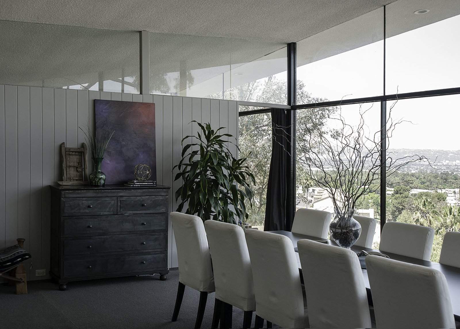 Dining Room, Chair, Carpet Floor, and Table Floor-to-ceiling windows provide sweeping city views.  Photo 5 of 13 in A 1958 Midcentury With Stunning L.A. Views Lists For $2.2M
