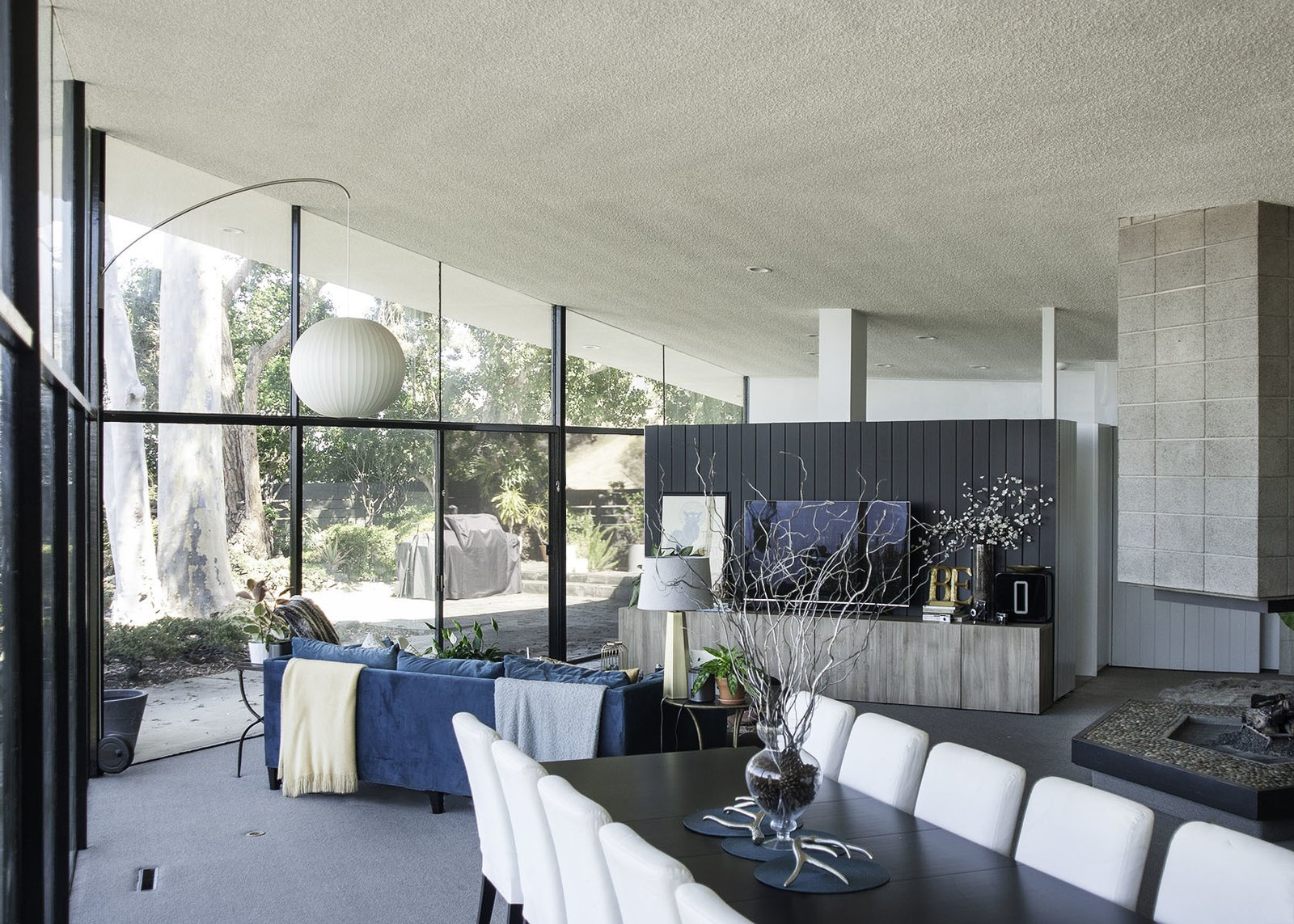 Living Room, Recessed Lighting, Chair, Table, Pendant Lighting, Sofa, Carpet Floor, Two-Sided Fireplace, End Tables, and Table Lighting  The stone fireplace anchors the open-plan living/dining room.      Photo 4 of 13 in A 1958 Midcentury With Stunning L.A. Views Lists For $2.2M