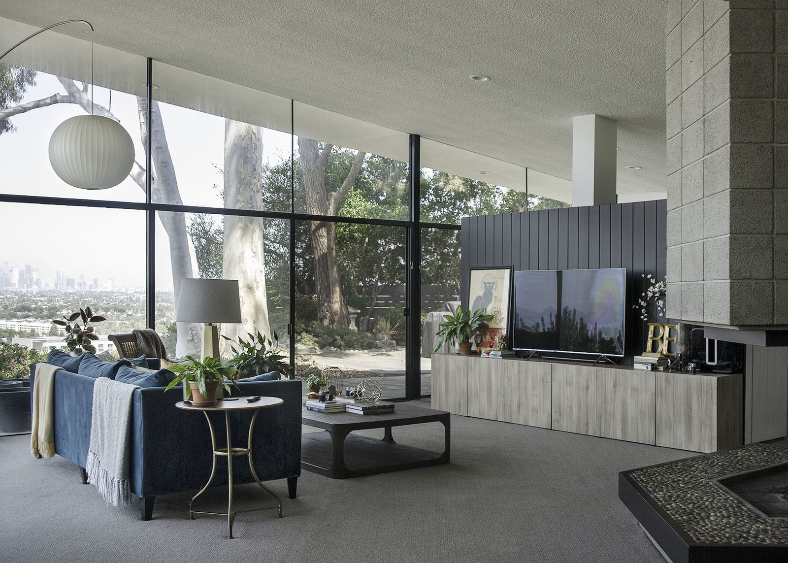 Living Room, Sofa, Chair, Recessed Lighting, Pendant Lighting, Carpet Floor, Two-Sided Fireplace, Coffee Tables, and Table Lighting Expansive walls of glass and sliding doors that lead to the large exterior patio create a strong sense of indoor/outdoor living.    Photos from A 1958 Midcentury With Stunning L.A. Views Lists For $2.2M