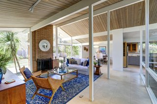 The open living/dining/kitchen area features a wall of glass, post-and-beam vaulted ceilings, Eichler's signature brick fireplace, as well as radiant floor heating throughout.