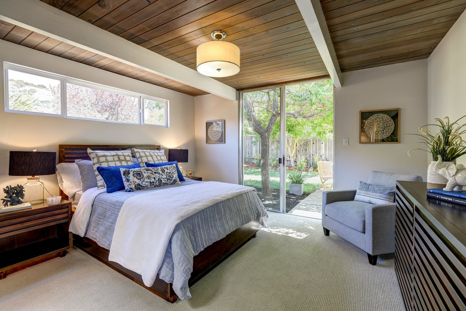 Bedroom, Carpet, Lamps, Floor, Chair, Ceiling, Bed, Dresser, and Night Stands The master suite has sliding doors that lead out to the exterior patio.     Bedroom Carpet Chair Ceiling Photos from A Bay Area Eichler With Custom Updates Hits the Market at $1.29M