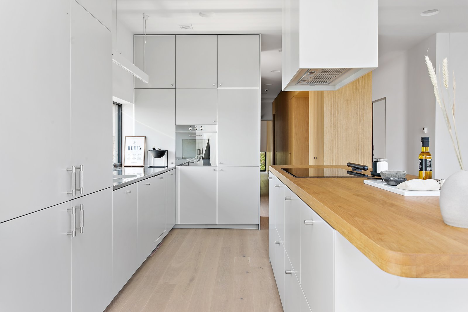 Kitchen, Light Hardwood, Wood, White, Wall Oven, Recessed, Range Hood, Cooktops, Drop In, and Pendant The kitchen features a sleek, modern mix of white millwork and natural wood countertops, and offers an impressive amount of storage.     Best Kitchen Cooktops Drop In Wall Oven Range Hood Light Hardwood Photos from Picture Yourself  in This Clifftop Swedish Retreat Asking $1.08M