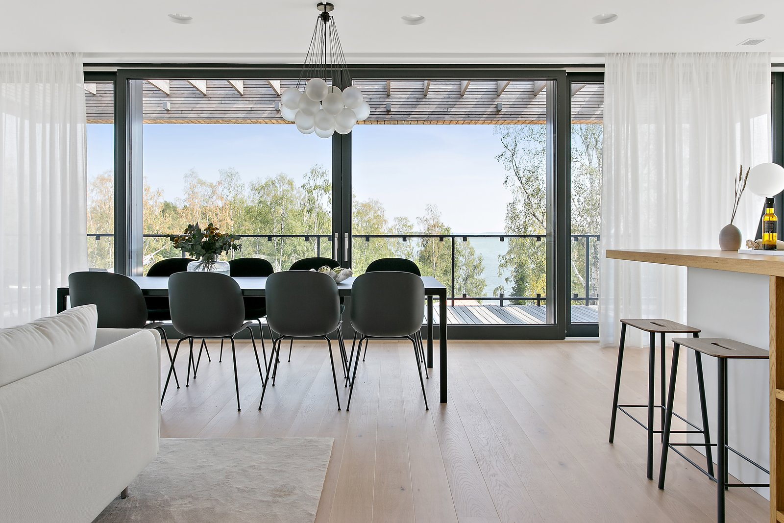 Dining, Pendant, Table, Light Hardwood, Chair, Stools, Rug, and Recessed The dining room table is perfectly positioned to enjoy the sweeping views of the Sörmlands archipelago.  Best Dining Table Recessed Stools Light Hardwood Photos from Picture Yourself  in This Clifftop Swedish Retreat Asking $1.08M