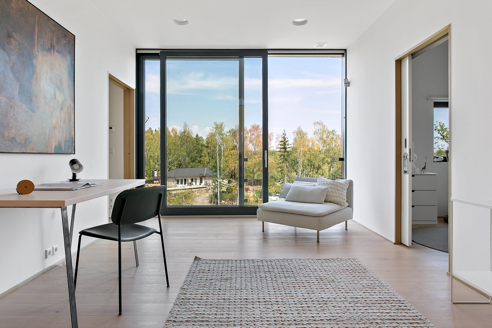 Living, Chair, Recessed, Light Hardwood, Desk, Table, and Rug A look at the small sitting room with sliding doors to the exterior.     Best Living Chair Desk Photos from Picture Yourself  in This Clifftop Swedish Retreat Asking $1.08M