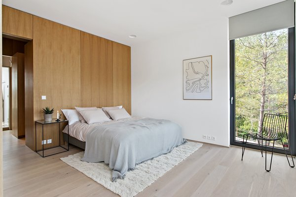 The mix of white juxtaposed against natural wood extends to the bedroom.