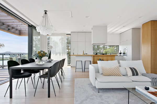 The bright and airy living room, dining area, and kitchen extend straight out to the wraparound terrace.