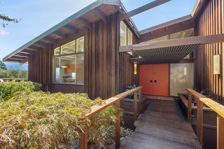 The entry of the wood-clad property features beautiful midcentury lines.