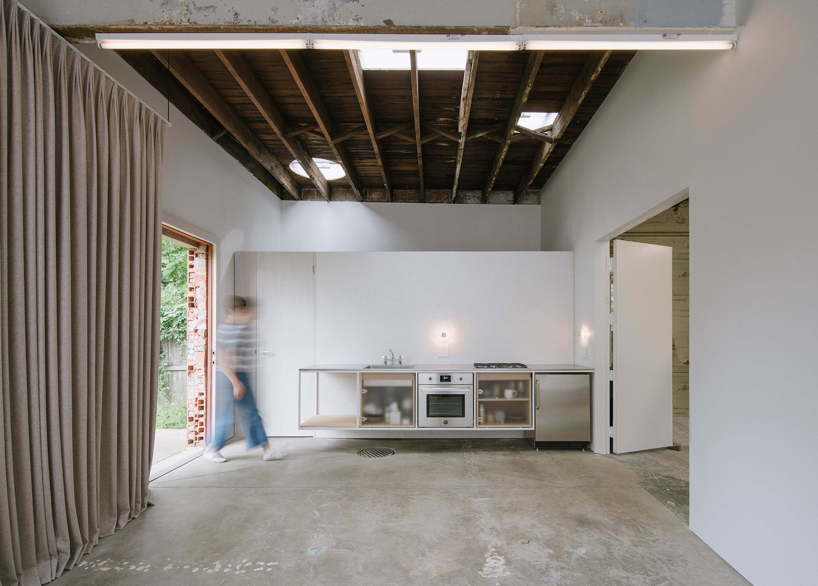 Kitchen, Wall Oven, Concrete, Ceiling, Range, Refrigerator, Wall, and Drop In Instead of clearing out the building and designing the interior from scratch, the designers Davidson and Rafailidis reinterpreted the existing space.  Best Kitchen Refrigerator Wall Oven Concrete Wall Photos from A 1920s Masonry Garage Is Reborn as a Flexible Live/Work Space