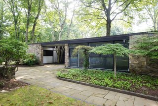 Set on a 7.7-acre lot, the 3,400-square-foot residence is both spacious and compact with a natural flagstone facade and black-stained cedar framing.