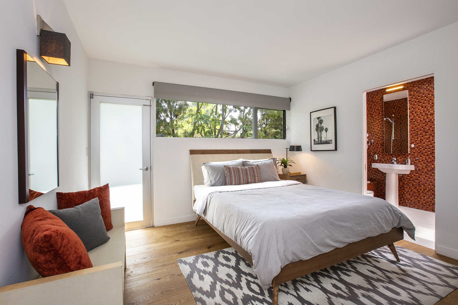 Bedroom, Medium Hardwood Floor, Bed, Wall Lighting, Night Stands, Bench, Table Lighting, and Rug Floor This bedroom features a beautifully tiled bathroom.  Best Photos from Fifty Shades Actor Jamie Dornan Lists His Midcentury Retreat at $3.2M