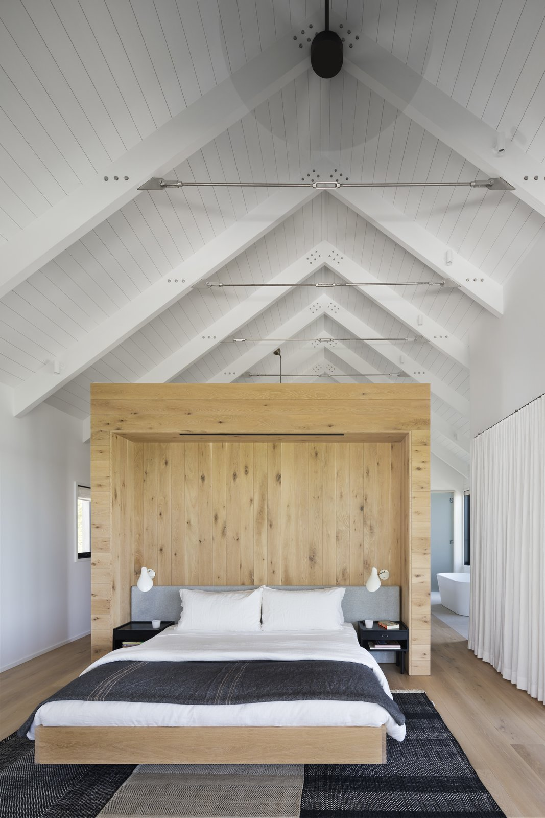 Bedroom, Night Stands, Light Hardwood, Wall, Rug, and Bed The master bedroom features vaulted ceilings and a light-wood wall to break up the space.     Best Bedroom Wall Rug Light Hardwood Bed Photos from Two Cedar-Clad Structures Form a Unique Montauk Retreat