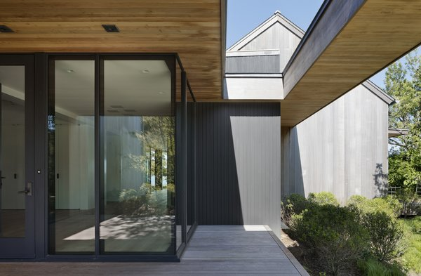 The overall rustic exterior is juxtaposed against a modern entry with a sleek profile.