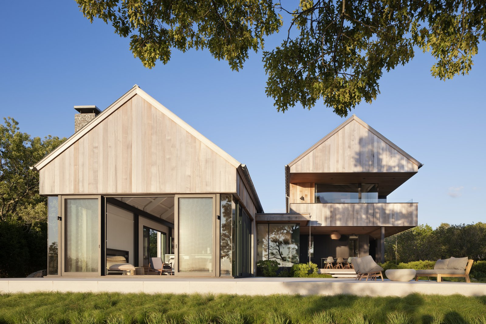 Exterior, Wood Siding Material, House Building Type, Beach House Building Type, Gable RoofLine, and Metal Roof Material East Lake House, designed by Robert Young Architects, features two structures to capture sunshine and breezes from all angles.  Best Photos from Two Cedar-Clad Structures Form a Unique Montauk Retreat