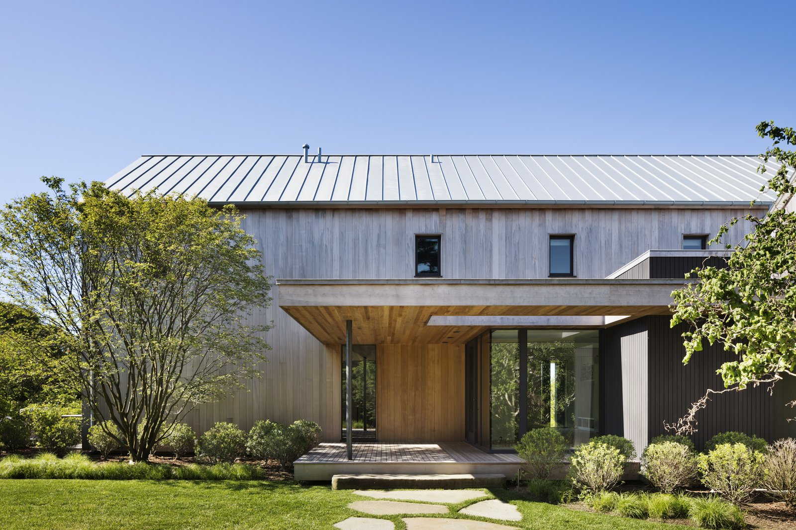 Exterior, Metal Roof Material, Beach House Building Type, House Building Type, Wood Siding Material, and Gable RoofLine The unfinished cedar planks will develope a silvery patina over time.  Best Photos from Two Cedar-Clad Structures Form a Unique Montauk Retreat