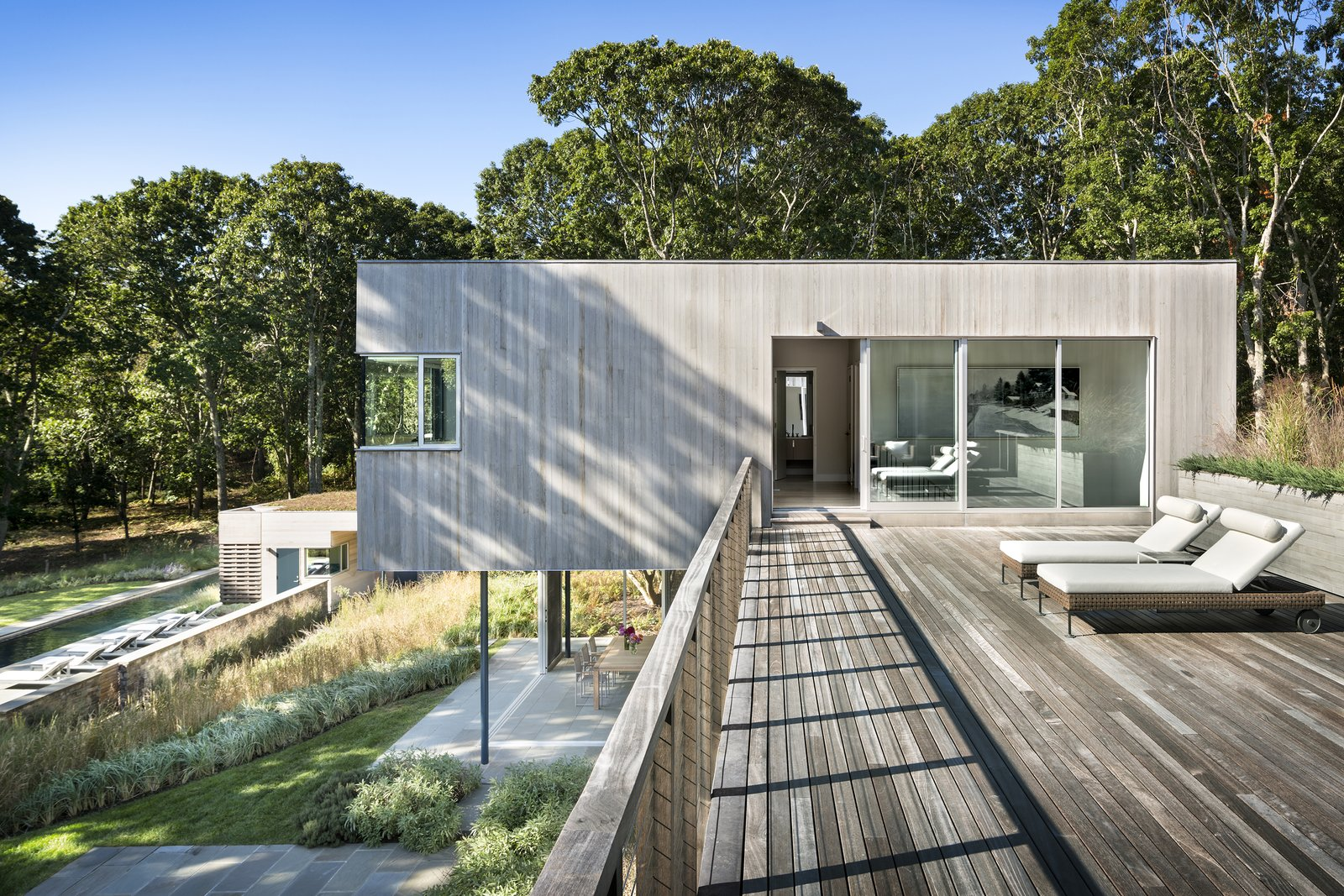 Outdoor, Shrubs, Rooftop, Large, Trees, Grass, and Horizontal The roof deck forms a connector between the two cedar-clad volumes, while also providing additional outdoor space.   Best Outdoor Trees Rooftop Photos from A Gorgeous Refuge Treads Lightly on its Surrounding Nature Reserve