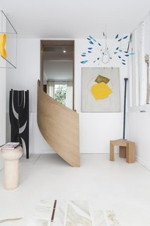 A sculptural staircase elegantly brings visitors down to an additional gallery space.