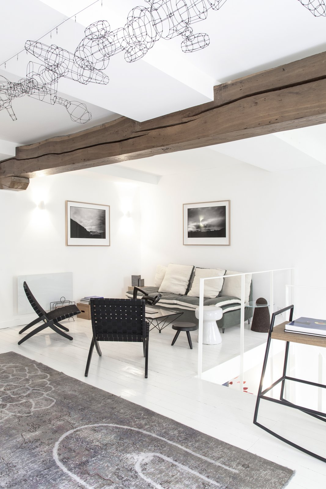 Living Room, Chair, Coffee Tables, Rug Floor, Sofa, Bench, and Light Hardwood Floor Floors have been covered by a thick coat of white paint.     Photo 7 of 14 in A Parisian Townhouse Is Reborn as a Luminous Art Gallery
