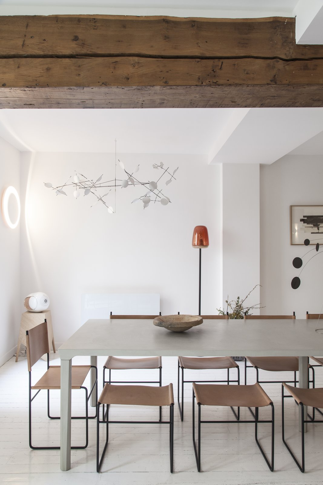 Dining Room, Light Hardwood Floor, Chair, Wall Lighting, and Table Exposed wooden beams add an element of warmth to the space.     Photo 5 of 14 in A Parisian Townhouse Is Reborn as a Luminous Art Gallery