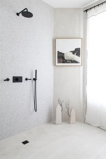 Even the terrazzo and concrete black-accented bathroom is a stunning showcase for the collection.  The shower has been left open since it will not be used.