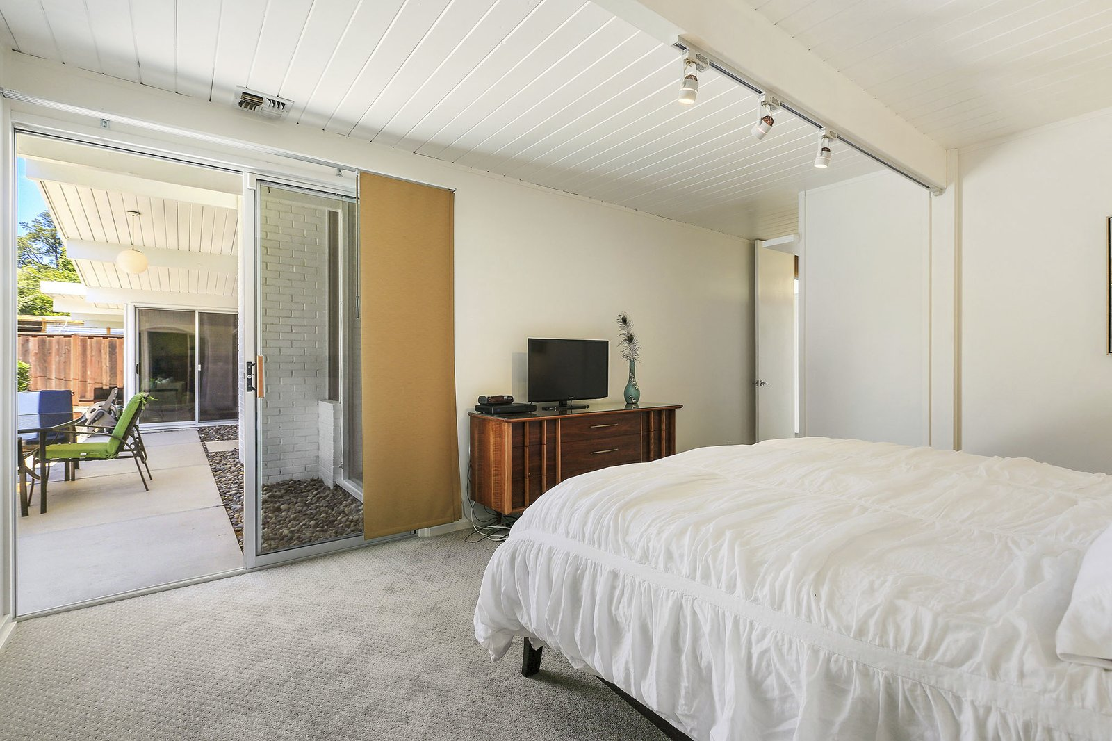 Bedroom, Dresser, Bed, Carpet, and Track The roomy master suite has an ensuite bathroom and outdoor access.  Best Bedroom Track Bed Photos from A Handsome East Bay Eichler Lists For $875K