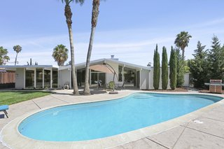 A 1964 home built by the iconic and prolific California developer, Joseph Eichler, features a kidney-shaped pool in the back yard. The lot is almost 10,000 square feet, and the fully enclosed backyard space is perfect for entertaining, featuring a kidney-shaped swimming pool and a hot tub.