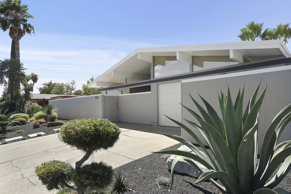 The meticulously landscaped front yard is low maintenance and features drought tolerant plants and a sprinkler system.