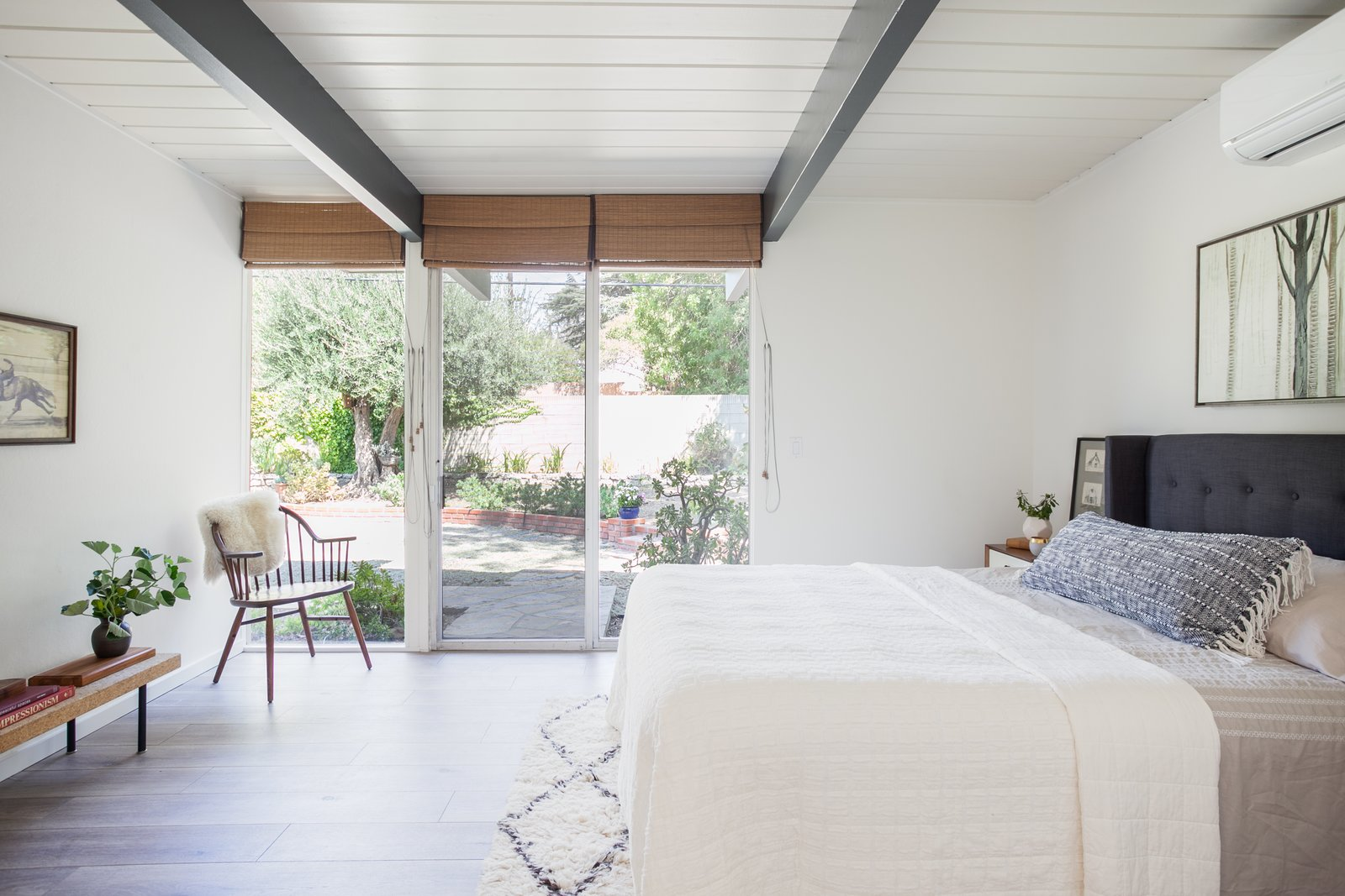 Bedroom, Bench, Bed, Rug Floor, Night Stands, Chair, and Medium Hardwood Floor The master bedroom features sliding doors that lead out to the backyard.    Photo 10 of 15 in An Updated Orange County Eichler Hits the Market at $1M