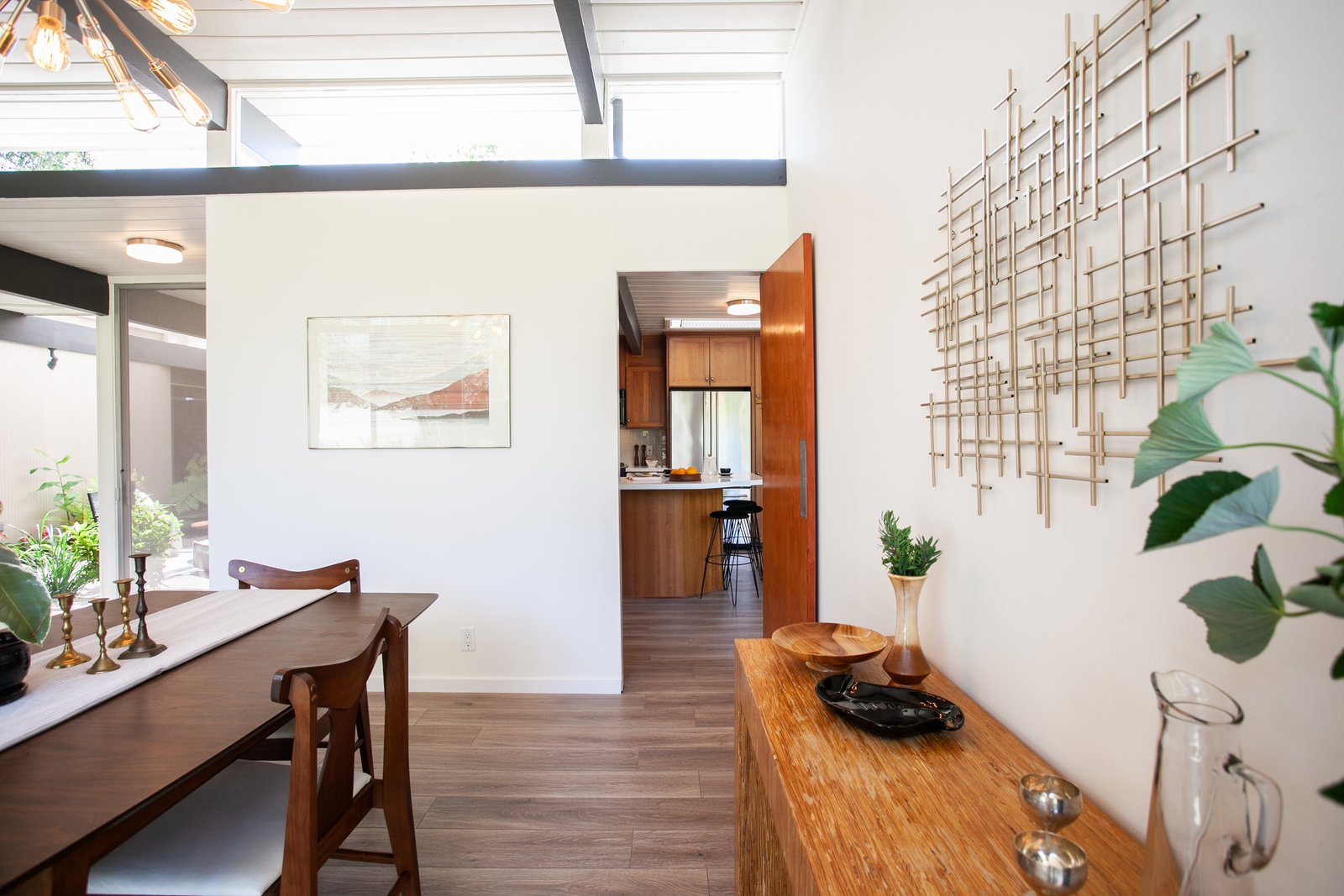 Dining Room, Chair, Accent Lighting, Table, and Medium Hardwood Floor While the kitchen can be closed off, it is also connected to the dining room, making for easy entertainment.     Photo 7 of 15 in An Updated Orange County Eichler Hits the Market at $1M