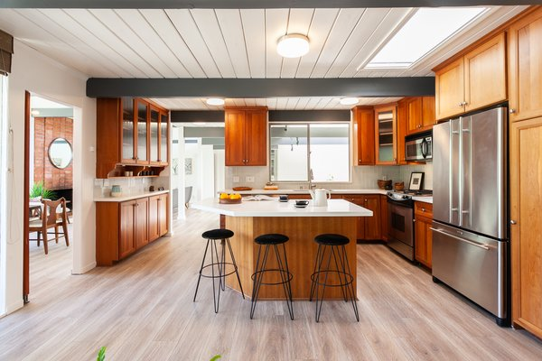 The updated kitchen includes stainless steel appliances and a center island with bar seating.